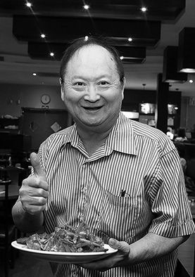Mature asian man giving thumbs up and holding a plate of food