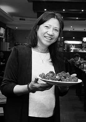 Mature asian woman holding a plate of food