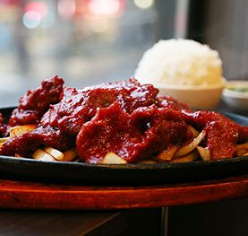 Beef on a sizzling plate and a bowl of rice