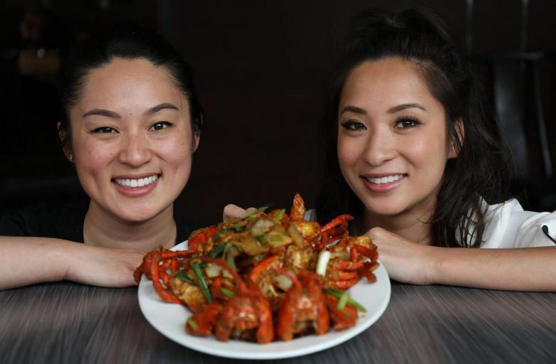 Two asian women with a plate of stir fried lobster